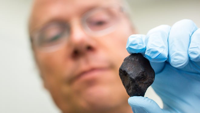 Laurence Garvie, curator of ASU's Center for Meteorite Studies, displays a meteorite he found on his recent trek (photo by Charlie Leight/ASU Now)