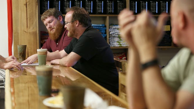 From left, mug club members Luke Thompson and Jesse Harris choose beers to order at the new Books & Brews location in Zionsville, Ind., during its soft opening for mug club members, Wednesday, June 29, 2016. The taproom and used bookstore is open to the public July 1, 2016.