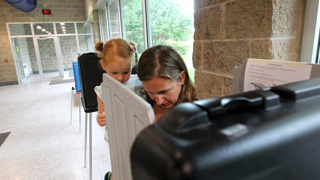 Kristin Wendlandt votes with help from her 3-year-old daughter, Eliza, at West High on Tuesday, July 19, 2016., in a special school board election for the Iowa City district.