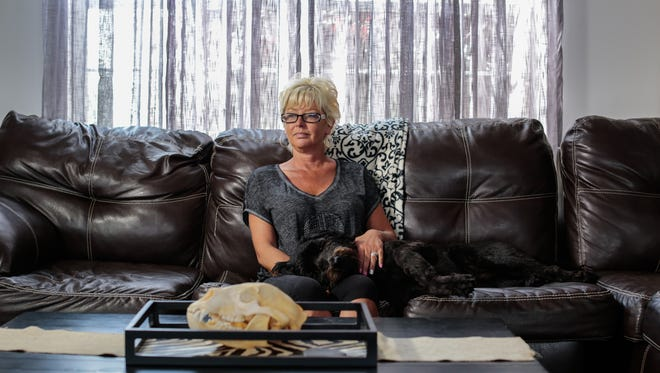 'This was my bed,' Lauralie Herkimer said while sitting with her dog Lilly at her home in Dundee on Friday July 8, 2016 after working multiple hours overtime in a week at the women's Huron Valley Correctional Facility. 'I would take quite a few shots of whiskey and go to sleep. Sleep for 3-3.5 hours and get up and go to work. There was days I slept on the couch four or five days in a row.'