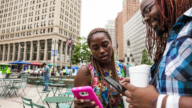 Ashley Ward of Dearborn Heights shows a Pokemon she caught to Patrick Hodges of Detroit while playing Pokemon Go during her lunch break at Campus Martius in downtown Detroit on Thursday July 21, 2016. Ward takes advantage of the amount of Pokemon and other items available in downtown Detroit compared to where she lives.