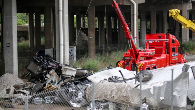 A semi truck lay on it's side after bouncing off the center wall, knocking a light pole into southbound traffic, bouncing back to the other side and going over the edge of the River Rouge bridge, damaging the guard rail at Dearborn street in Detroit on Sunday, July 24, 2016.