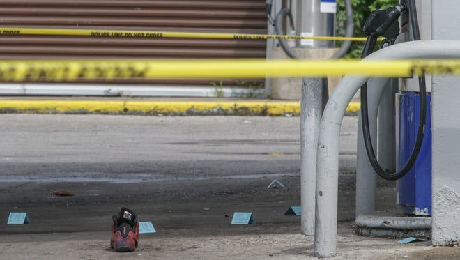 Police mark evidence at the scene of a shooting at the Clark Brands gas station at 38th and Oxford streets on Tuesday, July 26, 2016.