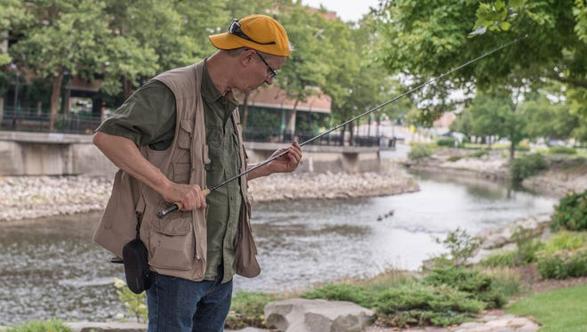 Paul Jakubiak assembles his fly-fishing rod before an event on the Battle Creek River to help people learn fly fishing and promote that the rivers in our area are a valuable asset.