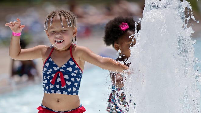 Left, Cyra Swanson, 3, splashes in a fountain at the Dr. Martin Luther King, Jr. park pool, Saturday, July 30, 2016.