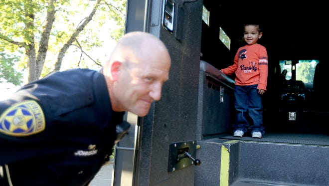 Jade Azcue, 3, climbs in a SWAT vehicle past Sgt. Mike Johnson during a National Night Out party on Donald St. NE in Salem on Tuesday, Aug. 2, 2016.