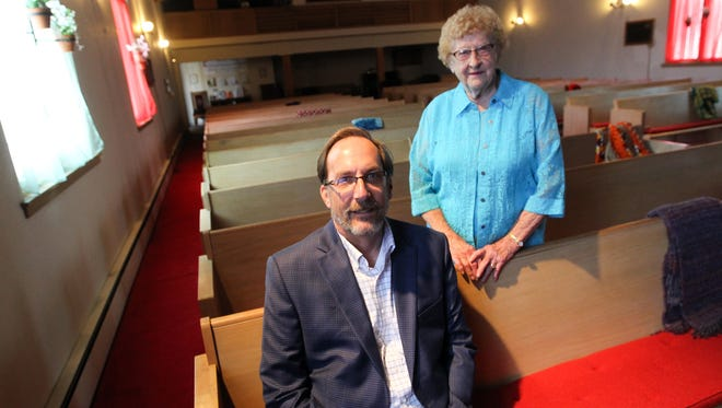 Sharon Center United Methodist Church Pastor Erling Shultz and lifelong member Marge Miller pose for a photo in the pews of the church in Sharon Center on Friday, Aug. 5, 2016. Four of Miller's great-grandparents helped found the church in 1866.