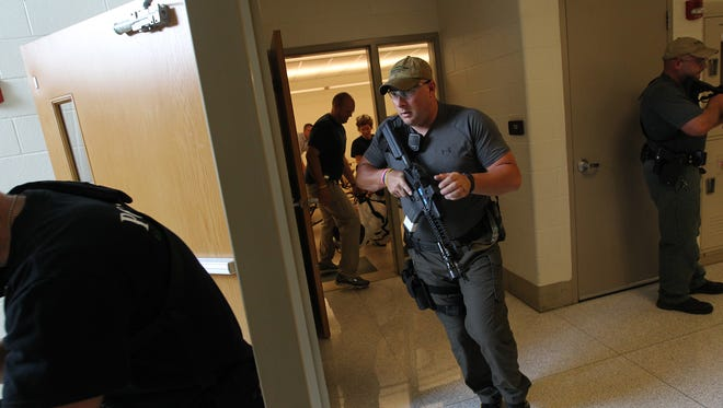 Coralville Police Officer Chad Wendel works with fellow officers and emergency responders during an emergency training exercise at West High on Wednesday, Aug. 10, 2016.