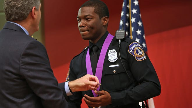 Officer Javed Richards, right, receives the Purple Heart from Interim Director of Public Safety David Wantz, left, and Chief of Police Rick Hite, not pictured, during the IMPD Honor Awards Program at the Central Library's Clowes Auditorium, Thursday, November 5, 2015.