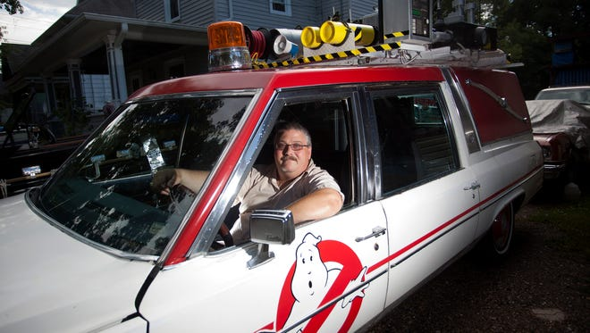 Aaron Aikman sits in a replica of the Ghostbusters hearse at his home in Lansing on Wednesday. He and Jerry Jodloski, of Lansing, teamed up to create the car, which is the same make and model hearse used in the new Ghostbusters film.
