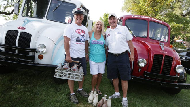 John Sterly, from left, and his wife, Annie Sterly, both of Lowell, stand with Gary Colosimo of Pittsburgh for a photograph in front of the Sterlys' 1964 Divco Model 300C milk delivery truck and Colosimo's 1957 Divco Model 13 in Royal Oak during the Woodward Dream Cruise on Saturday, Aug. 20, 2016.