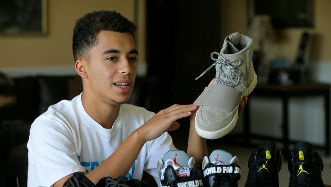 Dominick Ruiz, 16, of Manalapan, who started his own business on Instagram buying and reselling sneakers, displays some of his sneakers in Manalapan, NJ Monday August 22, 2016.  He holds an Adidas Kanye West 750 Boost sneaker.