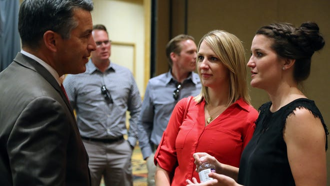 Gov. Brian Sandoval, left, talks to CAEK co-founder Katie Lay, far right, on Aug. 29 2016 in Reno.