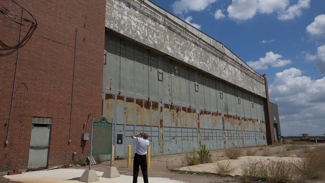 Tom Argiri, of Detroit, takes a photo of a historic marker  while getting a tour of Willow Run Bomber Plant hangar. A state Senate panel Wednesday approved a set of bills that will allow some of the adjacent land to be redeveloped as the American Center for Mobility, devoted to autonomous vehicle research and testing.