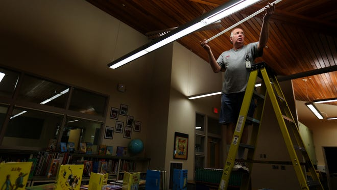 Electrician Tim McAllister changes out lightbulbs in the library at Lee Elementary School in Salem on Friday, Sept. 2, 2016. School begins for elementary students on Wednesday, with Kindergarteners beginning on Sept. 14.