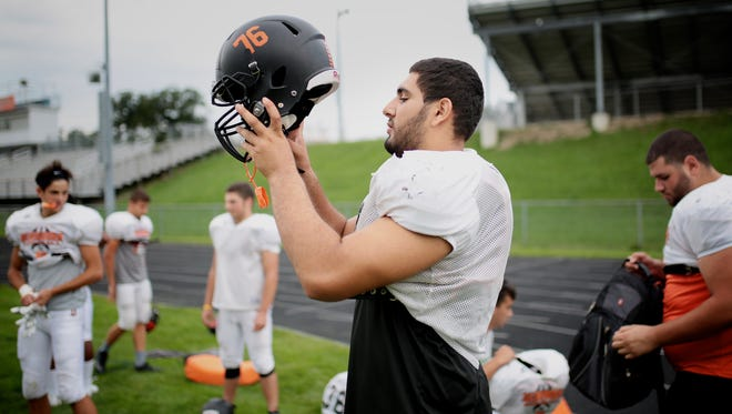 Mustafa Khaleefah, 17, of Dearborn, puts his helmet on at the start of practice on Tuesday, April 30, 2016, at Dearborn High School, in Dearborn, MI. Khaleefah didn't start playing football until his sophomore.
