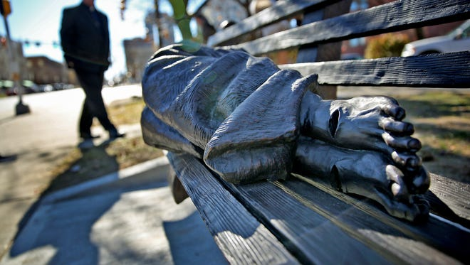 """A blanketed figure on a park bench, with bare and pierced feet, reflects """"Homeless Jesus,"""" a sculpture that sits outside Roberts Park United Methodist Church in Downtown Indianapolis to remind people of the homeless population."""