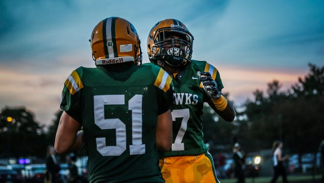 Farmington Hills Harrison Hawks's Cam Cooley, right, celebrates his touchdown with Theo Lucas against West Bloomfield on Friday in Farmington Hills.