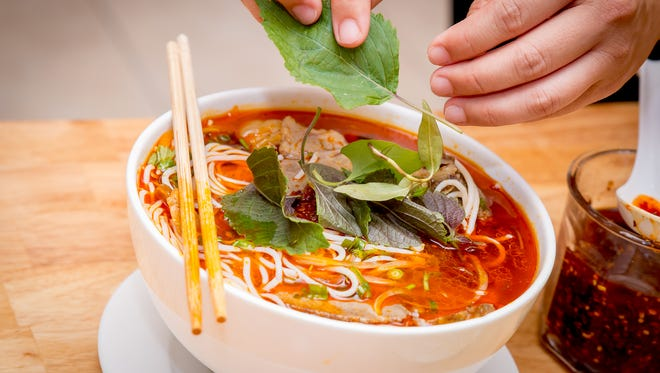 """Bun bo hue"" is a spicy beef soup with beef and pig's feet added with an assortment of homegrown herb condiments."