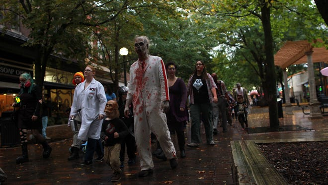 Zombies stroll through the pedestrian mall during the Iowa City Zombie March on Saturday, Sept. 28, 2013.   David Scrivner / Iowa City Press-Citizen