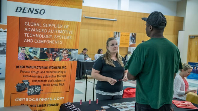 Denso Senior Specialist Nicole Brown talks to a perspective employee at BC Vision's job fair at the Kool Family Center on Thurday.