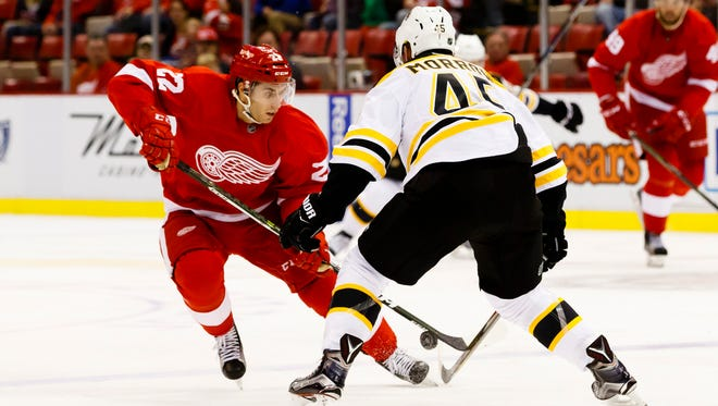 Red Wings right wing Matthew Lorito (22) skates with the puck defended by Boston Bruins defenseman Joe Morrow (45) in the first period of the exhibition game Friday at Joe Louis Arena.