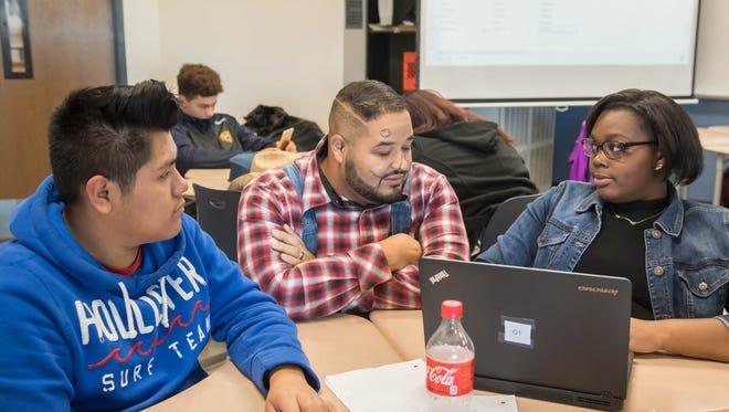 Battle Creek Central High School current events teacher Tyler Gilland (center) advises senior Luis Juarez (lt) and senior Carlee Templeton on articles for their new newspaper called BC Current.
