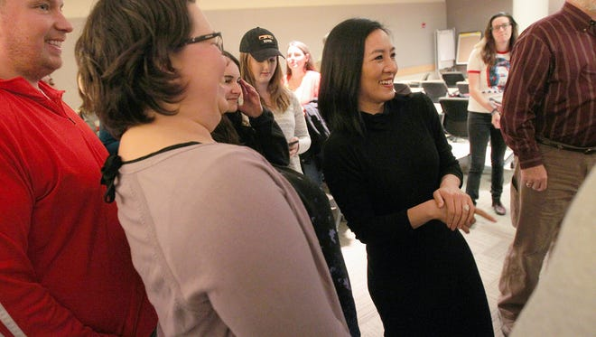 Olympic figure skater Michelle Kwan greets community members during a rally to promote early voting on Wednesday, Oct. 26, 2016, in Iowa City.