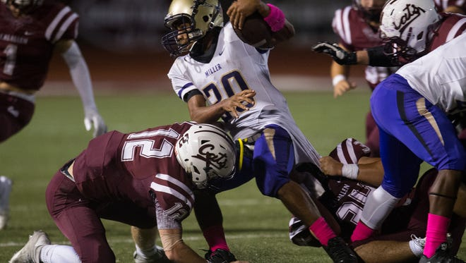 Miller's Raul Garcia is brought down by Calallen's Andrew Montelongo and Sam Allen as he runs the ball during the third quarter of their game at Wildcat stadium, Friday, Oct. 28, 2016.