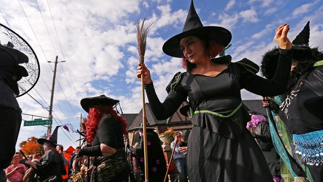 Witches from the Irvington Black Hat Society stop to dance and greet the audience at the corner of Audubon and Washington, during the costume parade at the Historic Irvington Halloween Festival street fair, Indianapolis, Saturday, October 29, 2016.