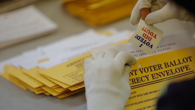 A worker adds stickers for absentee voters while preparing ballots to send out on Wednesday, Oct. 29, 2014, at the City of Detroit Department of Elections in Detroit.