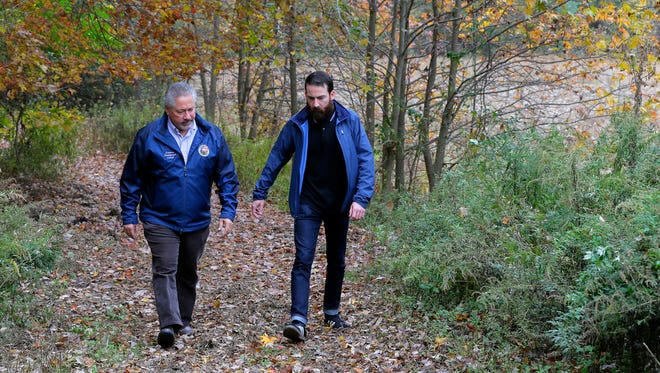 Glen Mendez and Ben Doda, two Manalapan residents who are trying to resurrect an old township plan to install miles of biking and walking trails around Manalapan, talk about the plan in the wooded area behind the Monmouth County Library  in Manalapan, NJ Thursday, November 3, 2016.