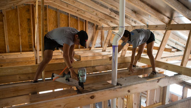 Del Mar College students Pablo Garcia and Alyssa Alvarado work in the rafters of a new home they are assisting Habitat for Humanity representatives build on Monday, Nov 7, 2016