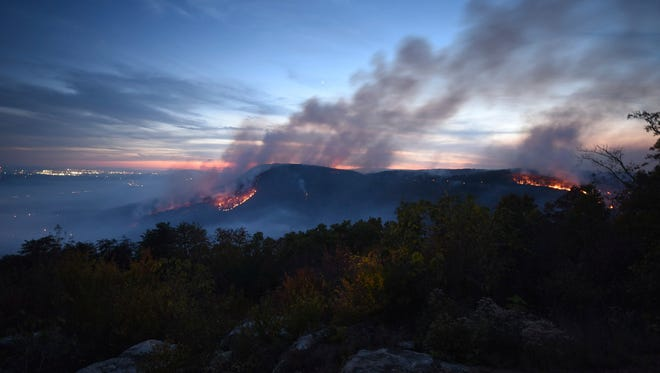In this Nov. 7, 2016, photo, two major fires burn at the Flipper Bend area atop Walden Ridge, seen from the Montlake neighborhood of Soddy-Daisy, Tenn.