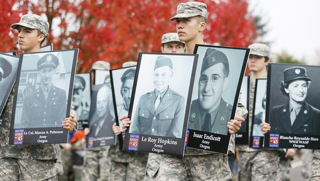 Members of a Junior ROTC program carry the photos of World War II veterans at a Veterans Day parade.