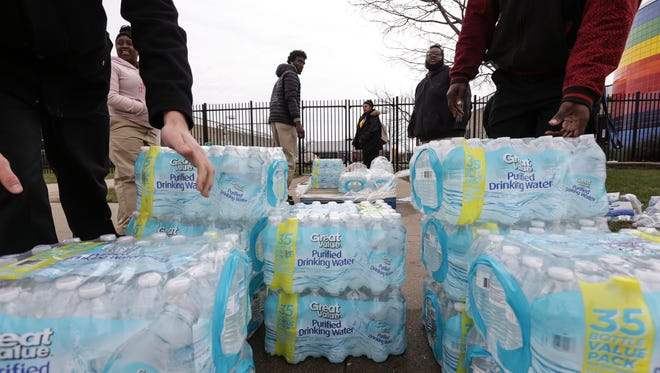 Flint / Genesee County Job Corps Center students gather cases of water to distribute at the school to those in need during the Flint water crisis on Wednesday March 30, 2016 at the Flint / Genesee County Job Corps Center. Water has been given-away on Wednesday's at the location on Saginaw Street for the past five months. The Food Bank of Eastern Michigan delivers ten pallets each Wednesday to be distributed. Residents are able to load up with as much water as they need.