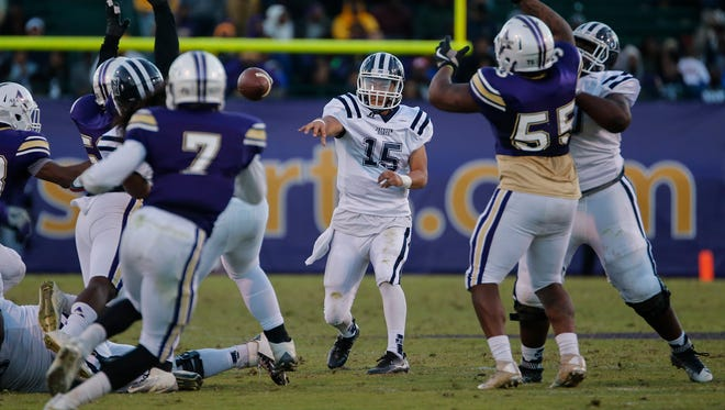 JSU quarterback Jarin Morikawa passes through the outstretched arms of Alcorn defenders.