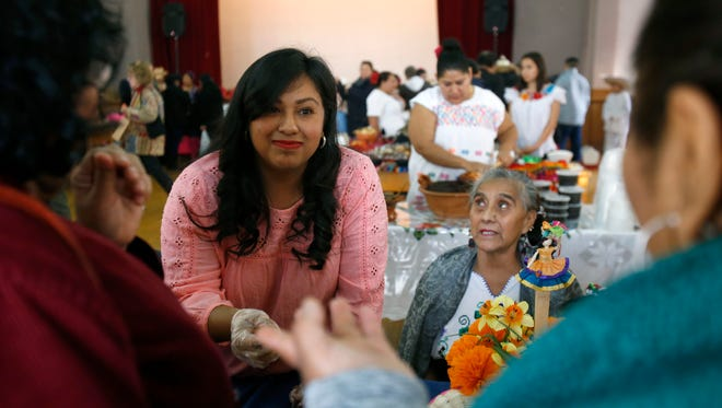 Maite Alcantara, center, helps her mother Crecencia Cruz, right, sell her homemade traditional Mexican mole during the second annual Holy Mole contest and event on Sunday afternoon Nov. 20, 2016 at St. Anne's Detroit church in Detroit.