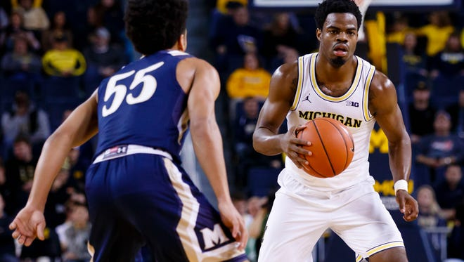 Michigan guard Derrick Walton Jr. (10) moves the ball defended by Mount St. Mary's guard Elijah Long (55) in the first half of U-M's 64-47 win over Mount St. Mary's Saturday at Crisler Center.