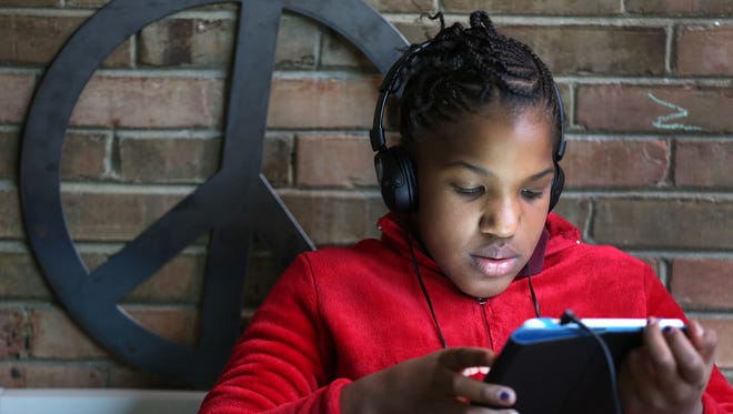 Jamyra Smith reads on a tablet in the Martin Luther King Community Center's Peace Room. The center is nestled in the middle of one of the IMPD targeted neighborhoods that has high incidents of crime, drugs and violence. The center created the Peace Room for children to find peace and quiet.