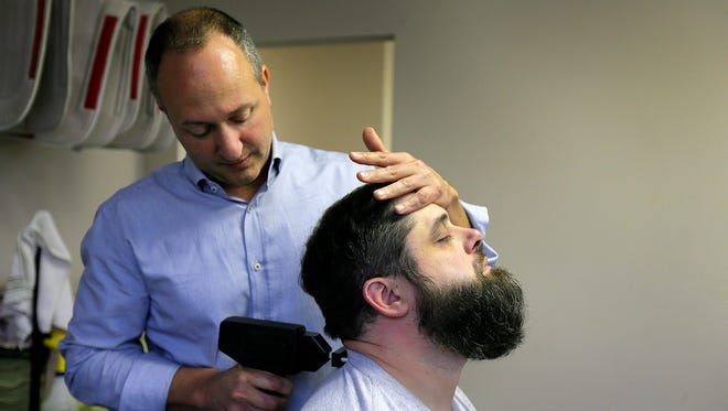 Tom Gustafson, a chiropractor who owns Active Healing Center, adjusts Nick DeMaria of Monroe Twp. using the Petition System at his practice in Colts Neck.