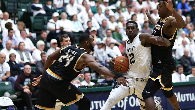 CSU's Emmanuel Omogbo fights his way through two Wichita State defenders on a drive to the basket in Saturday's game at Moby Arena.