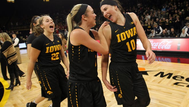 Iowa's Megan Gustafson, from right, Ally Disterhoft and Kathleen Doyle celebrate the Hawkeyes' 88-76 win over Iowa State at Carver-Hawkeye Arena on Wednesday, Dec. 7, 2016.