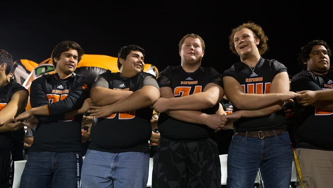 Refugio players stand for the fight song at Jack Sportsman Bobcat Stadium during a pep rally for their state championship.
