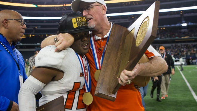 Refugio head coach Jason Herring holding the state championship trophy hugs quarterback Jacobe Avery after winning the Class 2A Division I state championship over Crawford 23-20 at AT&T Stadium in Arlington Texas on Thursday, Dec. 15, 2016.