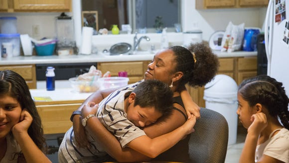 Sharicka McHenry, gives a hug to her son Angel Marcus
