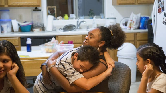 Sharicka McHenry, gives a hug to her son Angel Marcus McHenry, 10, at their home in Phoenix.