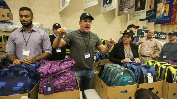 Mike Parker (center), CEO and founder of Next Phase Enterprises, gives out free backpacks to students at the Dream Center in the Family Dining Hall in December 2016.