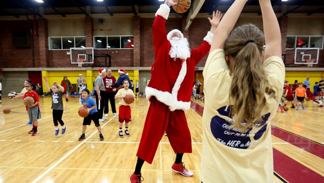 Kevin McShane, a former Oregon State basketball player, helps with a passing session while dressed as Santa Claus during the free kid's basketball clinic, part of the Capitol City Classic tournament, at Willamette University in Salem on Thursday, Dec. 22, 2016.