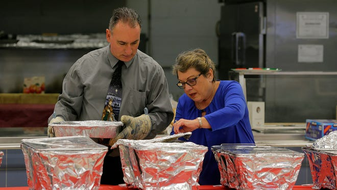 Marty McMahon of Middletown, parish deacon, and Jackie Kaszuba of Middletown, a volunteer, prepare for the Saint Mary, Mother of God Parish Christmas dinner inside the Saint Mary School cafeteria in Middletown, NJ Sunday December 25, 2016.